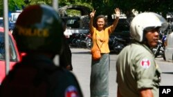 A Cambodian lawmaker from the main opposition party of Cambodia National Rescue Party (CNRP) Mu Sochua, center, gestures to make the number seven, the party's ballot number, before being detained by authorities at Freedom Park, in Phnom Penh, Cambodia, Tuesday, July 15, 2014. Three lawmakers from the opposition CNRP were detained and sent to police headquarters for leading about a hundred of their supporters to demonstrate in front of the park, asking authorities to open the site to the public. (AP Photo/Heng Sinith)