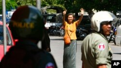 A Cambodian lawmaker from the main opposition party of Cambodia National Rescue Party (CNRP) Mu Sochua, center, gestures to make the number seven, the party's ballot number, before being detained by authorities at Freedom Park, in Phnom Penh, file photo.