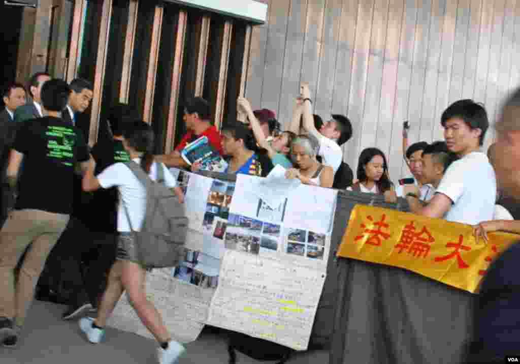 香港學聯幾名代表衝開特首辦門外示威區的鐵欄,走向特首梁振英要求直接對話,被多名保安人員阻止