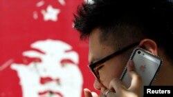 အိုင္ဖုန္း အသံုးျပဳေနေသာ ေဘဂ်င္းၿမိဳ႕မွ လူတစ္ဦး။ (ဓါတ္ပံု - REUTERS/Kim Kyung-Hoon)