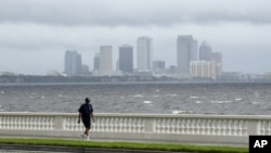 A resident walks along Bayshore Boulevard in between squalls blowing across the bay in Tampa, Florida, Monday, Aug. 27, 2012.