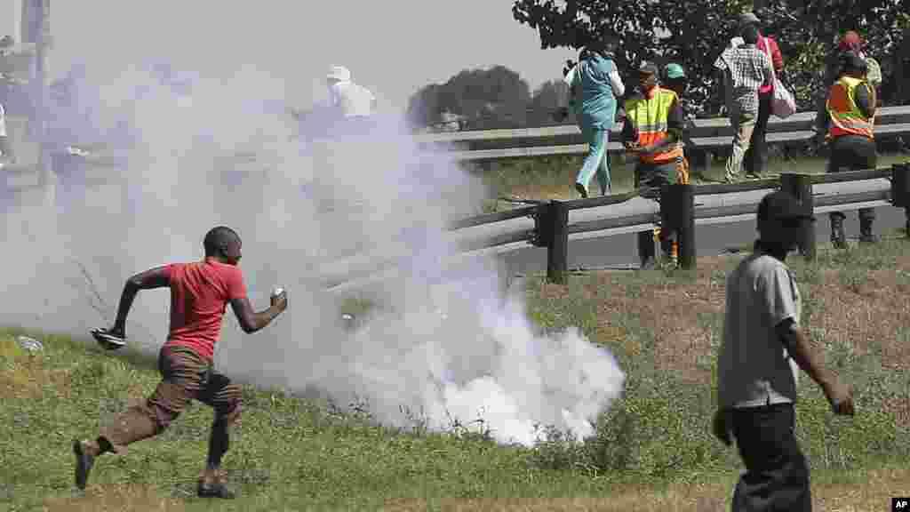 Wakazi wa kitongoji cha mashariki ya Johanesburg wakimbia wakati polisi wanafyetua mabomu ya kutoa machozi kuwatawanya waandamanaji wanaowapinga wageni.