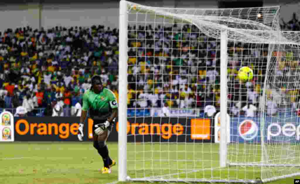 Gabon's Ebang looks on as Morocco's Kharja scores a penalty during their African Cup of Nations soccer match in Libreville