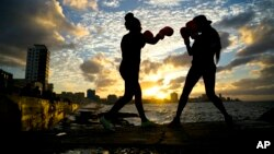 Boxers Idamelys Moreno, left, and Legnis Cala, train during a photo session on Havana's sea wall, in Cuba, Jan. 30, 2017.