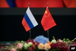 FILE - Russian, left, and Chinese flags sit on a table before a signing ceremony at the Great Hall of the People in Beijing, June 8, 2018.