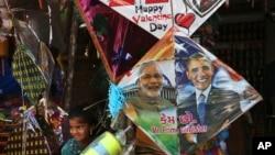 在印度海得拉巴的風箏節前夕,一名印度女孩站在一家店鋪出售的畫有印度總理莫迪和美國總統奧巴馬頭像的風箏邊。(2015年1月12日)