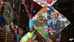 在印度海得拉巴的风筝节前夕,一名印度女孩站在一家店铺出售的画有印度总理莫迪和美国总统奥巴马头像的风筝边。(2015年1月12日)