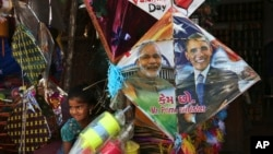 FILE - An Indian girl stands near a kite with portraits of India's Prime Minister Narendra Modi and U.S. President Barack Obama, for sale at a shop ahead of the Hindu festival Makar Sakranti, also known as kite festival, in Hyderabad, India, Jan. 12, 2015.