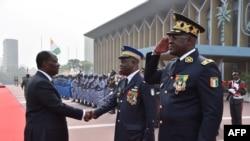 Le président ivoirien Alassane Ouattara, à gauche, salut le commandant en chef de la gendarmerie nationale ivoirienne, Nicolas Kouadio Kouakou, accompagné du directeur général de la police ivoirienne, Youssouf Kouyate, à droite, à Abidjan, le 4 janvier201