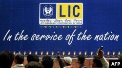 Người Ấn Độ xem 1 buổi biểu diễn nghệ thuật trước một biển quảng cáo của Công ty Bảo hiểm Nhân thọ Ấn Độ ở New Delhi, India, 25/11/2010