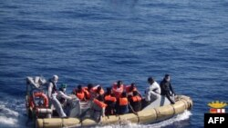 This handout picture released by the Italian Navy on June 6, 2014 shows migrants on boats being arrested and rescued by the Italian army off the coast of Sicily. The Italian navy on June 6 said it had rescued around 2,500 asylum-seekers in the Mediterranean.