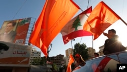 FILE - Lebanese supporters of the Free Patriotic Movement of Christian leader Michel Aoun wave the Lebanese and the party's orange flags as they ride their cars in the Christian stronghold of Metn north of Beirut, Lebanon, June 5, 2009.