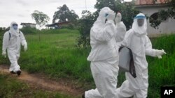 Health workers leave after they took a blood samples from a child to test for the Ebola virus in an area were a 17-year-old boy died from the virus on the outskirts of Monrovia, Liberia, June 30, 2015.