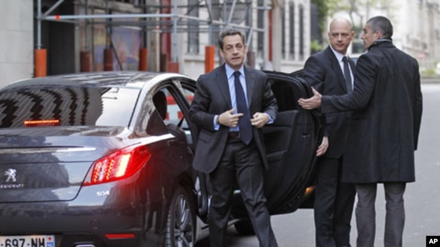 France's President and UMP party candidate for the 2012 French presidential elections Nicolas Sarkozy (L) arrives to attend an interview at the RTL radio station studios in Paris, April 20, 2012.