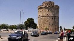 ເຈົ້າຂອງລົດແທັກຊີທີ່ພາກັນນັດຢຸດງານ ພວມຂັບລົດຜ່ານຫໍຄອຍສີຂາວໃນເມືອງ Thessaloniki ຊຶ່ງເປັນບ່ອນ ທ່ອງທ່ຽວທີ່ສຳຄັນ ໃນພາກເໜືອຂອງກຣີສ ຂະນະທີ່ພວກນັກທ່ຽວຫຼຽວເບິ່ງ (21 ກໍລະກົດ 2011)