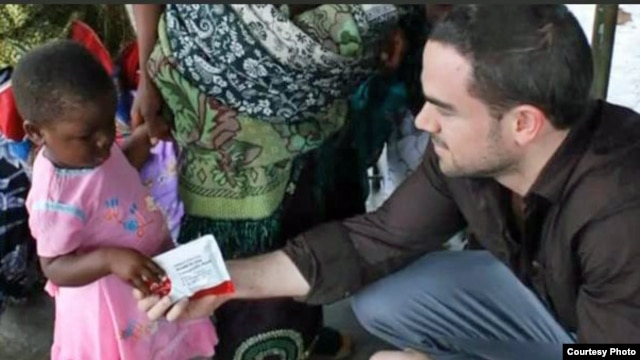 Two Degrees co-founder Will Hauser gives a prepared food packet to a child in Malawi. (Courtesy Two Degrees)