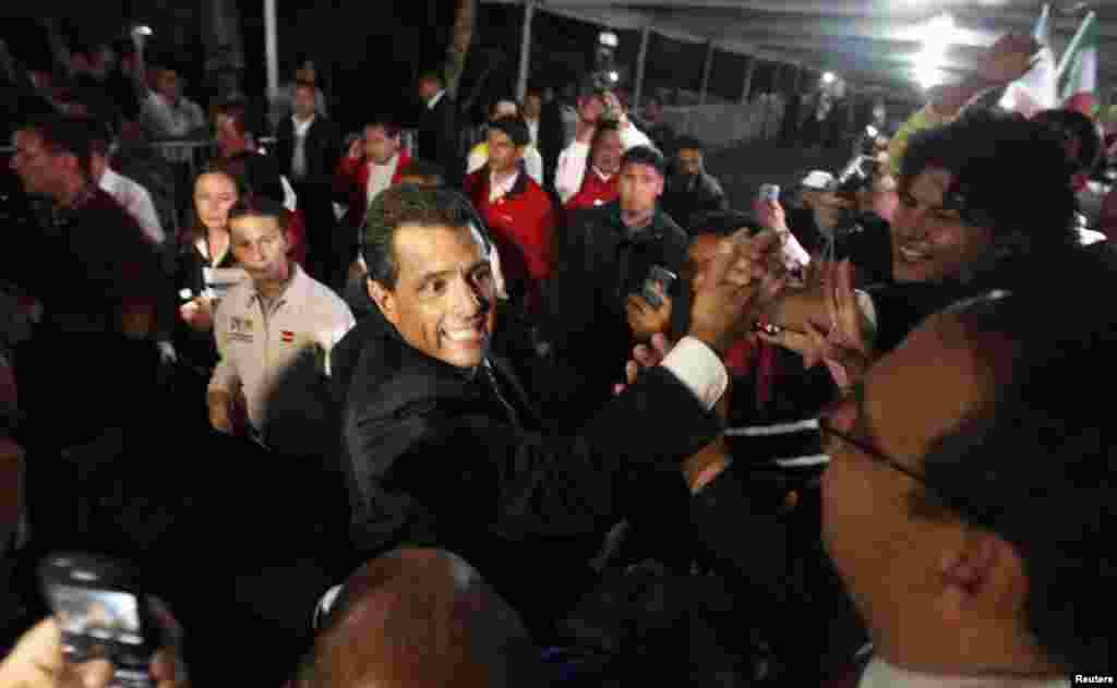 Enrique Pena Nieto greets supporters after exit polls showed him in first place, in Mexico City, July 1, 2012.