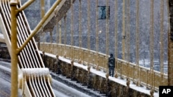 A man walks across the Rachel Carson bridge over the Allegheny River toward downtown Pittsburgh as snow falls during the evening rush hour, Jan. 20, 2016.