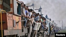 Penumpang bergelantungan di gerbong kereta yang sedang melaju di wilayah Utar Pradesh, India (Foto: dok) Kecelakaan kereta api sering terjadi di India.