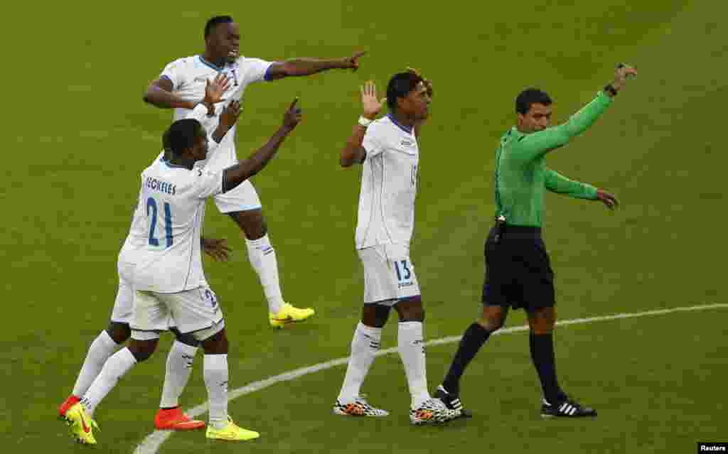 ہونڈوراس کے کھلاڑی ریفری ریکی کی طرف سے فرانس کو دیے جانے والے متنازعہ گول پر بحث کرتے ہوئے