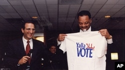 James Zogby and Jesse Jackson holding a T-shirt bearing the Arab American Institute's get-out-the-vote logo. 'Yalla' means 'Come on,' in Arabic.
