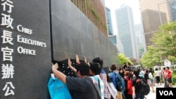 示威者在香港特首辦公室門外,掛上一幅貼有超過10萬名市民簽名的大型黑布,要求當局撤回國民教育科