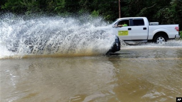 Motorists drive through a flooded street in Leonardtown, Maryland., after Hurricane Irene, Sunday, Aug. 28, 2011