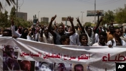 Protesters hold a banner calling for the release of political prisoners, during a march by members of the Sudanese medical profession syndicate, at the sit-in inside the Armed Forces Square, in Khartoum, Sudan, Wednesday, April 17, 2019.