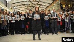 People hold portraits and printed names of victims of the Tu-154 plane, which crashed into the Black Sea on its way to Syria on Sunday, during a memorial event in Rostov-On-Don, Russia, Dec. 26, 2016.