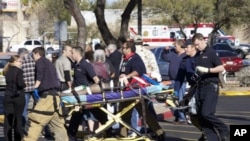 Emergency personnel use a stretcher to carry a shooting victim outside a shopping center in Tucson, Arizona, 08 Jan 2011