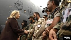 La secretaria de Estado, Hillary Clinton, saluda a los soldados del CNT, al descender del avión militar C-17 en el que viajó a Trípoli.