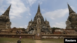FILE - Tourists walk at the ruins of the ancient capital of Ayutthaya, Thailand, Dec. 25, 2015. International tourist arrivals in Thailand are expected to reach a record high in 2016, the tourism minister said on Jan. 6, 2016, after nearly 30 million foreigners came to its temples, beaches and bars in 2015.