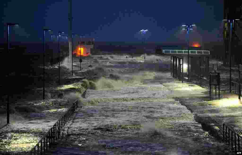 Waves lash the ferry pier on the North Sea coast in Dagebuell, Germany, as storm front Xaver hits the country.