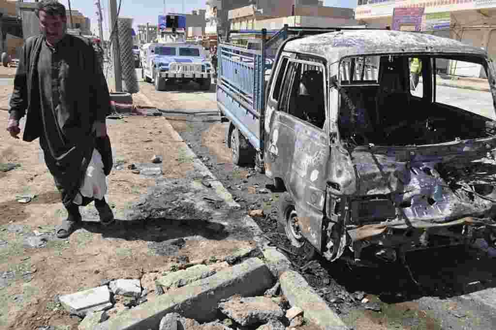 Seorang pria menghampiri mobil yang rusak dihantam bom di Ramadi (AP).
