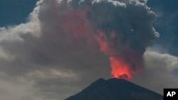 El cráter del Monte Agung brilla por la lava durante una erupción mientras arroja humo volcánico en Karangasem, isla de Bali, en Indonesia, el viernes 29 de junio de 2018. Bali cerró el viernes su aeropuerto internacional, dejando varados a miles de viajeros, cuando el volcán lanzó una columna de ceniza y humo de 2.500 metros de alto (8.200 pies). (Foto AP)