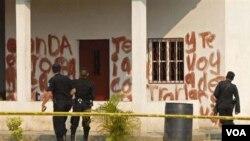 Agentes de la policía observan el mensaje pintado en la hacienda en el Caserío La Bomba, en La Libertad, al norte de Guatemala.