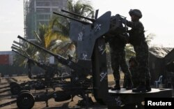 Philippine Marines check an anti-aircraft weapon mounted near the venues of the Asia-Pacific Economic Cooperation (APEC) summit during a security preparation in Manila, Nov. 14, 2015.