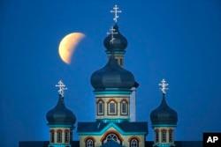 Fenomena yang dikenal sebagai supermoon tampak di akhir gerhana bulan di belakang geraja Ortodoks di Turets, Belarusia, 110 kilometer sebelah barat ibukota Minsk, Senin 28 September 2015.