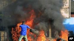 在科特迪瓦首都阿比让,反对派领导人瓦塔拉的支持者举行抗议,一名男子向火中扔轮胎