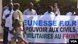 A soldier walks past Malians protesting the junta's arrest of several prominent figures in April