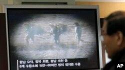 Du khách Hàn Quốc xem báo cáo trên truyền hình về các tù nhân Bắc Triều Tiên gần làng đình chiến Bàn Môn Điếm ở Paju.