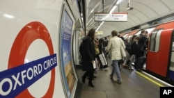 FILE - People board an underground 'Tube' train at Oxford Circus underground station in London.