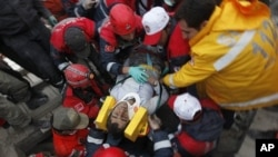 Emergency service workers carry an earthquake survivor during rescue operations in Ercis, near the eastern Turkish city of Van, October 24, 2011.
