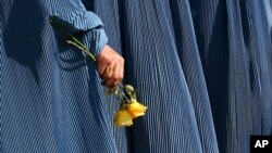 An Afghan woman holds flowers during a fair to mark Women's Day in Kabul, Afghanistan, March 8, 2007. At the time, roughly two out of five Afghan marriages were forced, and 45 percent of women are married by the age of 18. According to UNIFEM, at least on