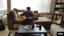 자택에서 민속악기 '탄부르'를 연주하고있는 루크만 아흐마드.