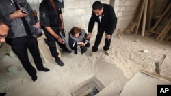 """In this photo provided by Mexico's attorney general, authorities inspect the exit of the tunnel they claim was used by drug lord Joaquin """"El Chapo"""" Guzman to break out of the Altiplano maximum security prison in Almoloya, west of Mexico City, July 12, 201"""