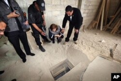 "FILE - In this photo provided by Mexico's attorney general, authorities inspect the exit of the tunnel they claim was used by drug lord Joaquin ""El Chapo"" Guzman to break out of the Altiplano maximum security prison in Almoloya, west of Mexico City, July 12, 201"