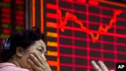 26일 중국 베이징의 증권거래소에서 투자가가 증시 현황을 지켜보고 있다.