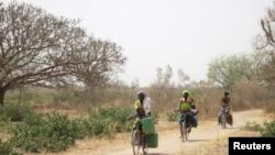 Une femme ramène de l'eau dans des bidons sur son vélo en direction du village de Bagare, dans la province de Passore, nord du Burkina Faso, le 30 mars 2016.