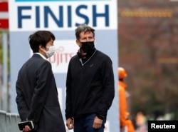 Kepala Organisasi Atletik Dunia Sebastian Coe (kanan), mengenakan masker, menyaksikan Hokkaido-Sapporo Marathon Festival 2021, acara pengujian lomba maraton Olimpiade Tokyo 2020, 4 Mei 2021. (REUTERS)